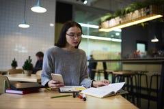La muchacha morena en vidrios realiza el sitio web diario del entrenamiento de trabajo que se sienta con efectos de escritorio y  Fotos de archivo libres de regalías