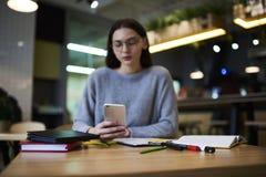La muchacha morena en vidrios realiza el trabajo diario con los ficheros de las multimedias de los seguidores, foco selectivo en  Fotografía de archivo libre de regalías