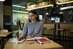 La muchacha morena en vidrios realiza el trabajo diario después de lecciones en la cafetería moderna que observa la información a Fotografía de archivo libre de regalías