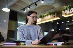 La muchacha morena en vidrios realiza el trabajo diario para aumentar renta de servicio y las ventas que trabajan sentarse en zon Imagen de archivo