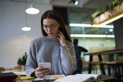 La muchacha morena en vidrios realiza el trabajo diario para crear la conexión a internet inalámbrica y el smartphone del uso del Fotografía de archivo libre de regalías