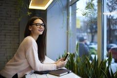 La muchacha morena en vidrios realiza el trabajo diario que descansa en cafetería usando Internet inalámbrico y panel táctil Fotos de archivo libres de regalías