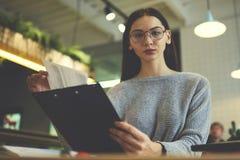 La muchacha morena en vidrios realiza el trabajo diario que lee el cv y la recomendación de los patrones anteriores que buscan el Fotos de archivo libres de regalías