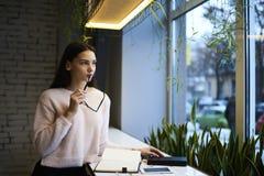 La muchacha morena en vidrios realiza el trabajo diario que pasa tiempo después de la lección en espacio coworking con wifi Fotos de archivo libres de regalías