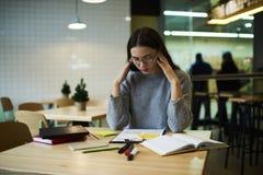 La muchacha morena en vidrios realiza el trabajo diario que se sienta en cafetería mientras que espera a los compañeros de clase  Foto de archivo