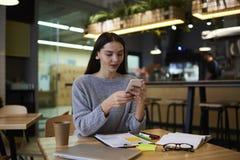 La muchacha morena en vidrios realiza el trabajo diario usando el uso en el smartphone conectado con el wifi Foto de archivo
