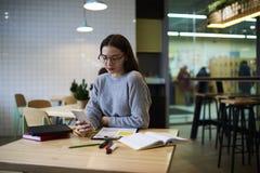 La muchacha morena en vidrios realiza el trabajo diario usando Internet inalámbrico y el smartphone que se sienta en cafetería Imagenes de archivo