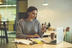 La muchacha morena en vidrios realiza el trabajo diario usando Internet y la tecnología a la estrategia del ` s de la organizació Imagen de archivo