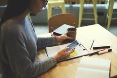 La muchacha morena en vidrios realiza el trabajo diario vía el smartphone conectado con el mejor amigo que espera de Internet ina Imagen de archivo