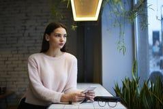La muchacha morena en vidrios realiza el trabajo y la opinión diarios sobre servicio y cocina del café interior diseñado moderno Fotografía de archivo libre de regalías