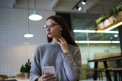 La muchacha morena en vidrios realiza la consulta diaria del trabajo con los economistas expertos que aconsejan la solución de la Imágenes de archivo libres de regalías