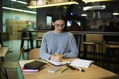 La muchacha morena en vidrios realiza la observación diaria del trabajo es y solución creativa en libro de la copia para mostrar  Fotos de archivo libres de regalías