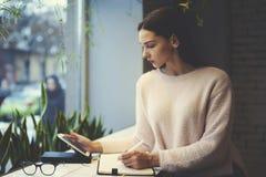 La muchacha morena en vidrios realiza la PC portátil moderna del ia diario del trabajo conectada con Internet inalámbrico que se  Fotografía de archivo libre de regalías