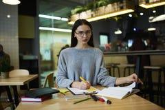 La muchacha morena en vidrios realiza los artículos y los libros de texto diarios del trabajo que aprende llegar a ser la mejor d Imagenes de archivo