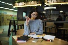 La muchacha morena en vidrios realiza los expedientes diarios del trabajo que fijan las blancos para el trabajo de supervisión de Imágenes de archivo libres de regalías