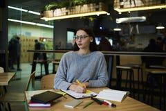 La muchacha morena en vidrios realiza servicio diario del trabajo y la fabricación de informe de la contabilidad que comprueba el Imagen de archivo