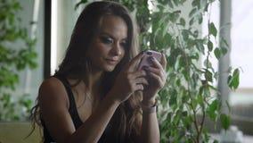 La muchacha morena encantadora está mecanografiando en una pantalla táctil de su smartphone, sentándose en restaurante en d3ia almacen de metraje de vídeo