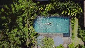 La muchacha morena está nadando en piscina al aire libre en el chalet entre las plantas tropicales almacen de video