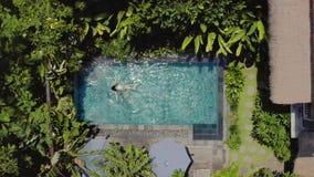 La muchacha morena está nadando en piscina al aire libre en el chalet entre las plantas tropicales almacen de metraje de vídeo