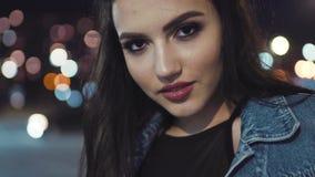 La muchacha morena europea magnífica que presenta justo antes de la cámara, toca su pelo, sonríe atractivo Maquillaje natural metrajes