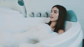 La muchacha morena feliz disfruta del baño por completo de la espuma en Jacuzzi bañera Relájese Reclinación almacen de metraje de vídeo