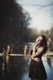 La muchacha morena hace una pausa el árbol cerca del agua Fotografía de archivo libre de regalías