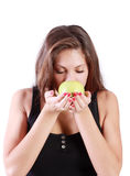 La muchacha morena hermosa con los ojos cerrados huele la manzana verde Fotos de archivo