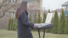 La muchacha morena hermosa del retrato apasionada sobre jugar el sintetizador y canta mientras que se coloca debajo del árbol en almacen de metraje de vídeo