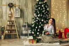 La muchacha morena hermosa es abre el regalo en la Navidad Imágenes de archivo libres de regalías