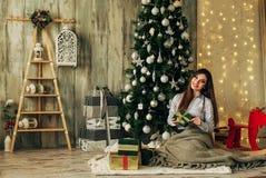 La muchacha morena hermosa es abre el regalo en la Navidad Foto de archivo libre de regalías