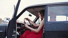 La muchacha morena hermosa está dentro de un coche del vintage, sosteniendo el volante almacen de metraje de vídeo