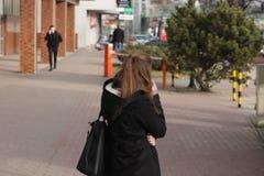 La muchacha morena hermosa joven comunica en un smartphone con un individuo en una calle de la ciudad Artilugios en amantes diari fotografía de archivo libre de regalías