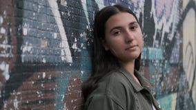 La muchacha morena hermosa joven se coloca cerca de la pared con la pintada que mira la cámara y la sonrisa almacen de metraje de vídeo