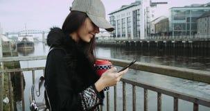 La muchacha morena hermosa que se coloca en el terraplén del río con el teléfono, lee el mensaje 4K almacen de metraje de vídeo