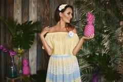 La muchacha morena hermosa y de moda con los ojos azules, en vestido amarillo con la piña rosada en su mano, está presentando en  imagen de archivo