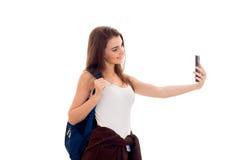 La muchacha morena joven alegre del estudiante con el backpackand azul y el teléfono móvil en sus manos hace el selfie aislado en Imagenes de archivo