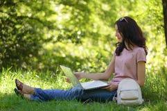 La muchacha morena joven con el ordenador portátil al aire libre está trabajando Fotografía de archivo libre de regalías