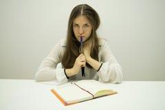 La muchacha morena joven con el pelo que fluye se sienta en una tabla con un diario en la tabla imagen de archivo libre de regalías