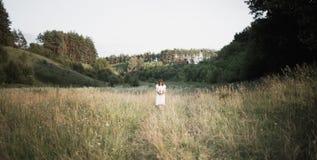 La muchacha morena joven con el ramo en el vestido blanco se coloca en el campo con su cabeza abajo Proceso retro de la foto Fotos de archivo