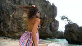 La muchacha morena joven en un vestido brillante corre a lo largo de la playa blanca, sonriendo en la cámara, desarrollando el pe almacen de metraje de vídeo