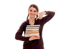 La muchacha morena joven feliz del estudiante en deporte marrón viste con muchos libros en sus manos que sonríe en la cámara aisl Foto de archivo