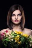 La muchacha morena joven guarda las flores en fondo negro Foto de archivo