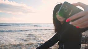 La muchacha morena joven hace el selfie que se sienta en la playa rocosa por el mar almacen de metraje de vídeo
