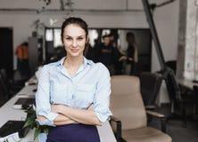 La muchacha morena joven sonriente vestida en ropa del estilo de la oficina se está colocando en la oficina moderna fotografía de archivo