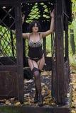 La muchacha morena llena grande hermosa en ropa interior, medias y ramillete del negro en metal viejo de las ruinas adornó e Foto de archivo libre de regalías