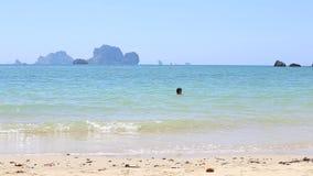 la muchacha morena nada en el mar contra las islas rocosas metrajes