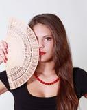 La muchacha morena oculta mitad de su cara por la fan Foto de archivo