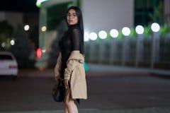 La muchacha morena presenta contra la ciudad de igualaci?n de la noche, las luces coloridas ilumina las ventanas que hacen compra fotos de archivo libres de regalías