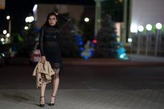 La muchacha morena presenta contra la ciudad de igualaci?n de la noche, las luces coloridas ilumina las ventanas que hacen compra imagenes de archivo