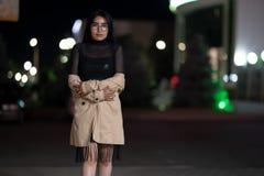 La muchacha morena presenta contra la ciudad de igualaci?n de la noche, las luces coloridas ilumina las ventanas que hacen compra imagen de archivo libre de regalías